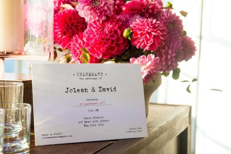 Wedding Invite With Vintage Typewriter Font Against Pink Flower Centerpiece | PartySlate