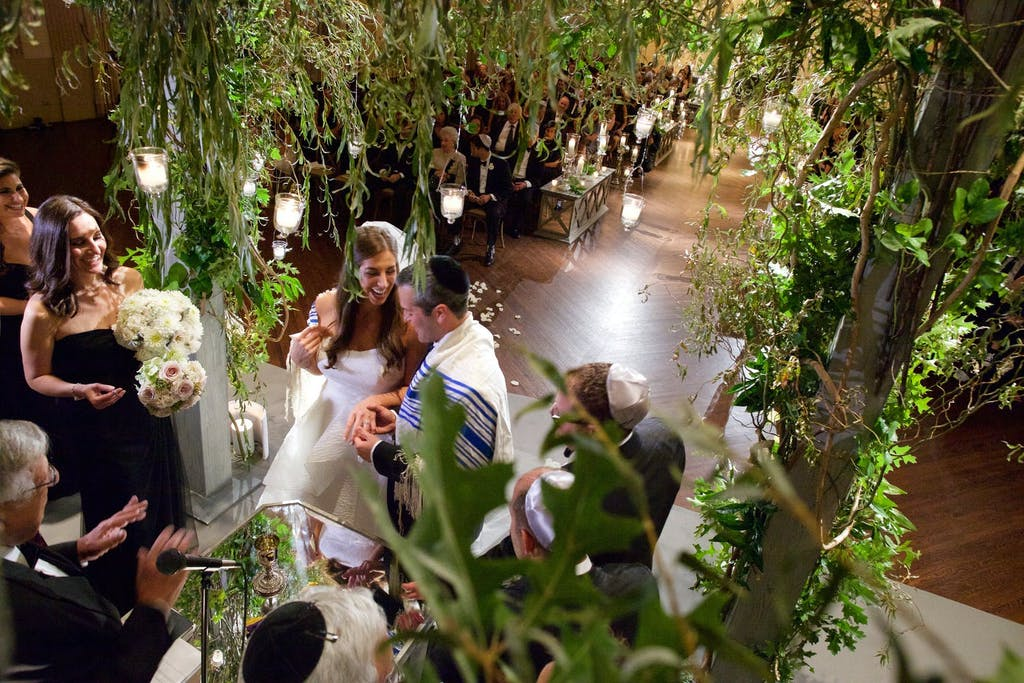 Wedding Ceremony Seen Through the Branches of the Chuppah | PartySlate