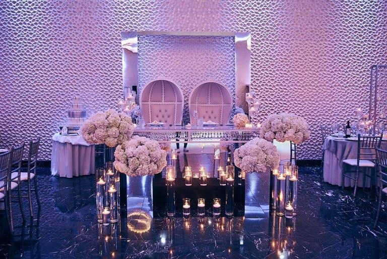 Purple Uplit Wedding With Modern Sweetheart Table Featuring Mirrored Elements, Candlelight, and Unique Seating | PartySlate
