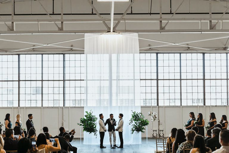 Wedding Ceremony With Modern Wedding Décor and Shimmering Drapery Backdrop | PartySlate