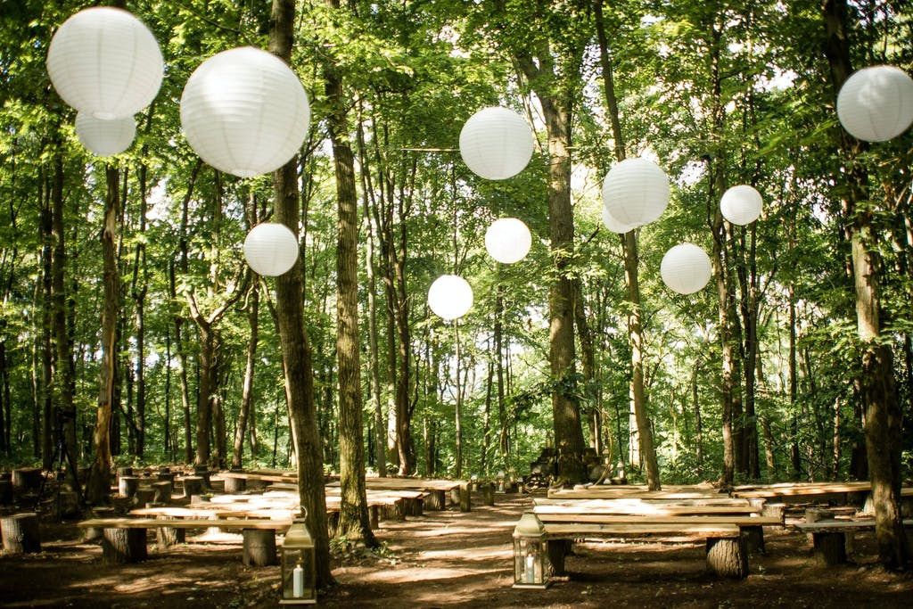 Outdoor enchanted forest wedding ceremony With White Paper Orbs Suspended in Treetops | PartySlate