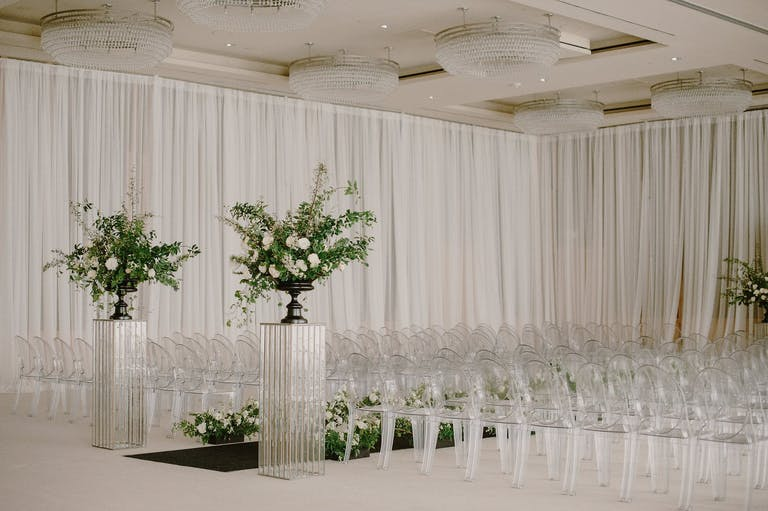Monochromatic Light Gray Ceremony With Modern Wedding Décor Elements Like Lucite Floral Stands, Gray Drapery, and Ghost Chairs | PartySlate