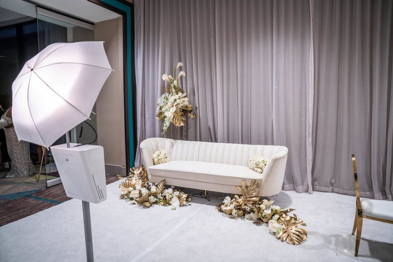 Minimalist Modern Wedding Décor Photo Op With White Sofa and Gold Florals | PartySlate