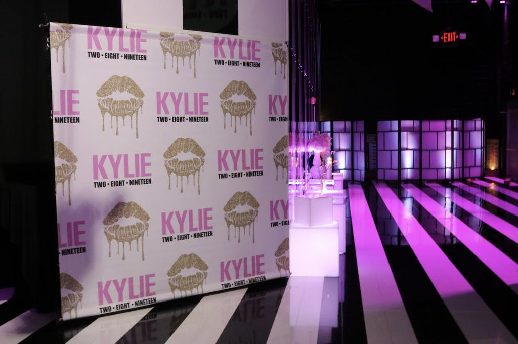 Gold Kiss Step and Repeat and Black and White Dance Floor With Pink Uplighting at Sweet 16 Party | PartySlate