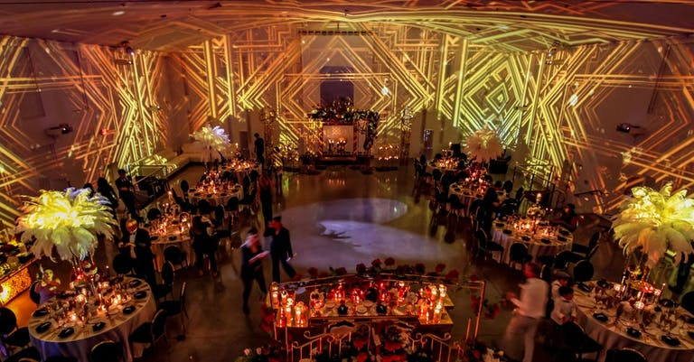 A Gatsby Party With Gold Art Deco Illuminating Against the Walls | PartySlate