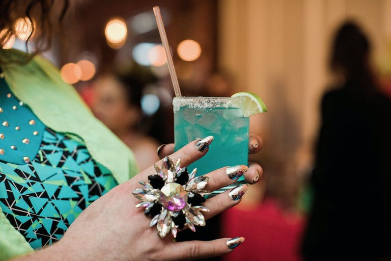 Hand Wearing Flashy Ring Holds a Neon Blue Cocktail | PartySlate