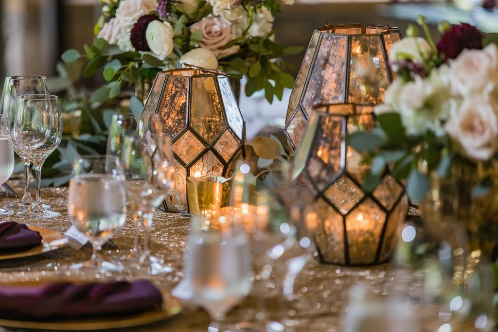 Wedding Tablescape With Vintage Lantern Candlelight and Burgundy Napkins | PartySlate