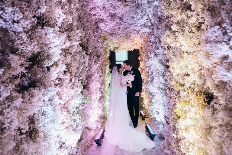 Bride and Groom Kiss in Wedding Entrance Made of Pure Baby's Breath | PartySlate
