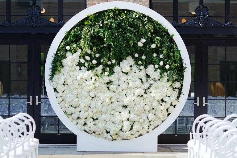 Modern Circular Wedding Arch Filled With Half Greenery and Half White Flowers | PartySlate