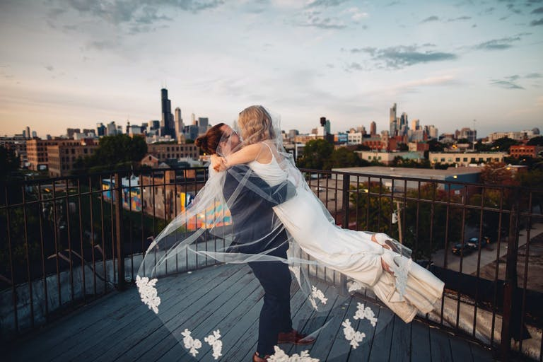 Bride and Groom Kiss Atop of Skydeck at Lacuna Events by LM Gallery | PartySlate