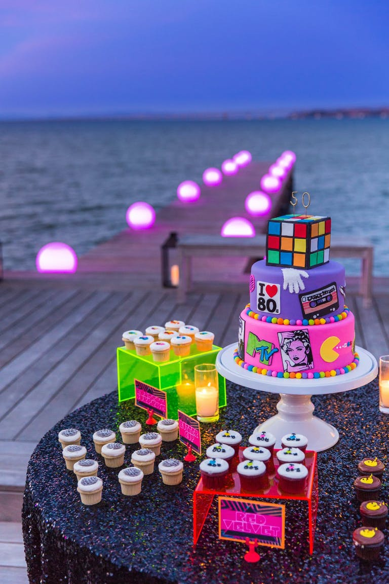 Beach Scene With Wooden Pier With Pink Neon Lights and 80s Party Dessert Station | PartySlate
