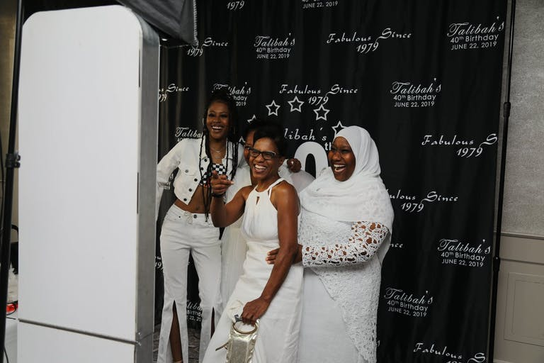 Guest, Dressed in White, Pose in Photo Booth at 40th-Birthday Party | PartySlate