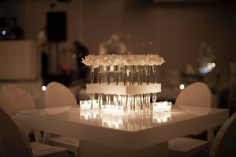 Modern Wedding All-White Wedding Tablescape With Square of Long-Stemmed White Flowers and Candlelight | PartySlate