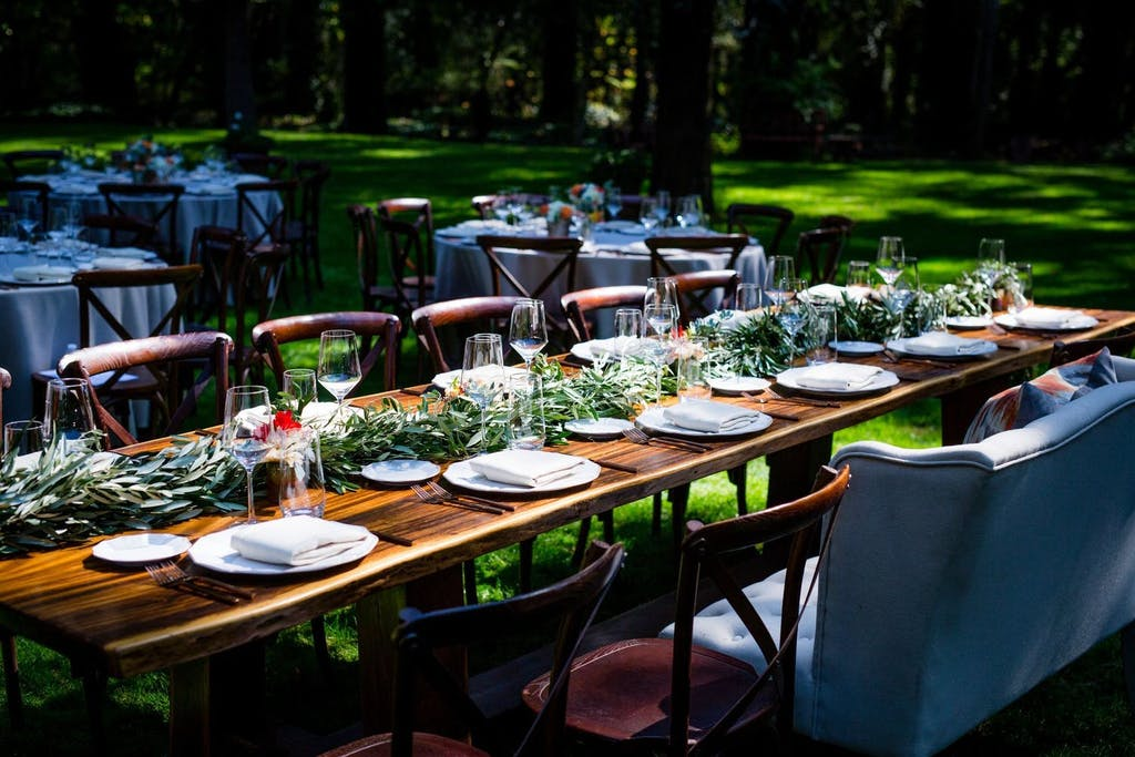 Outdoor Forest Wedding With Wooden Table and Garland Greenery Runner | PartySlate
