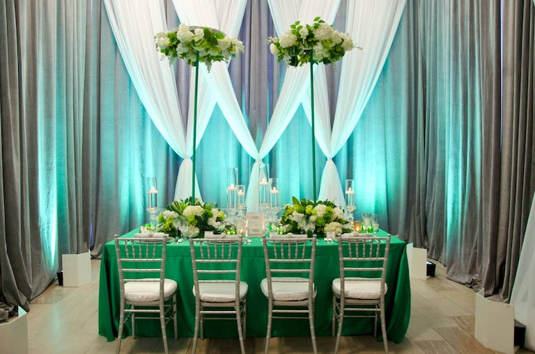 Modern Wedding Tablescape With Green Linen, Elevated Parasol-Like Greenery Centerpieces, and Sheer White, Green, and Gray Wall Draping | PartySlate