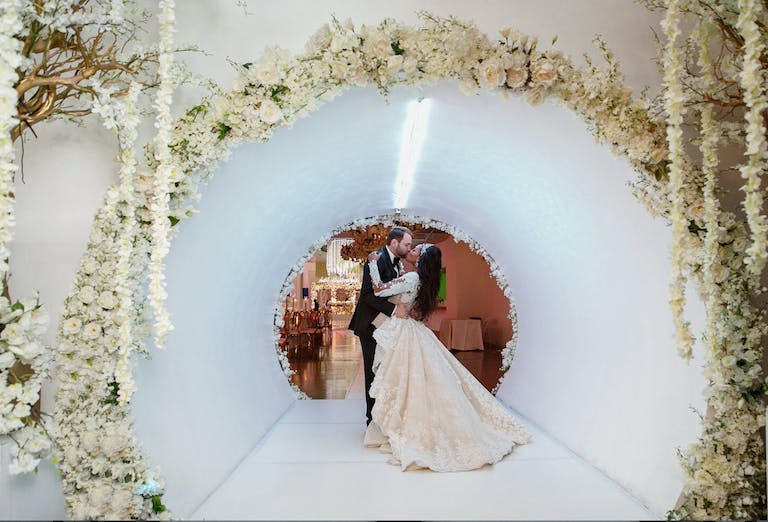 Bride and groom Kiss in Sleek White Tunnel Wedding Entrance With White Flowers | PartySlate