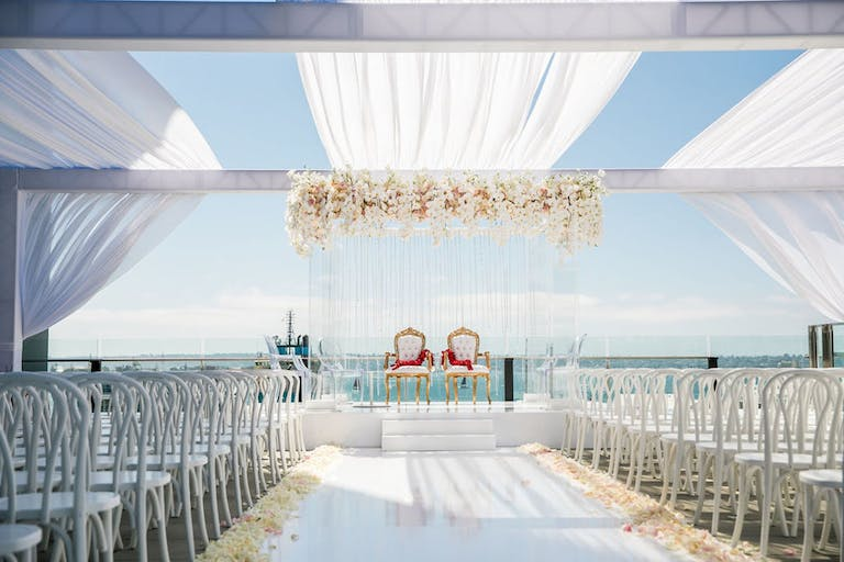 White beach side wedding with white linings and florals | PartySlate