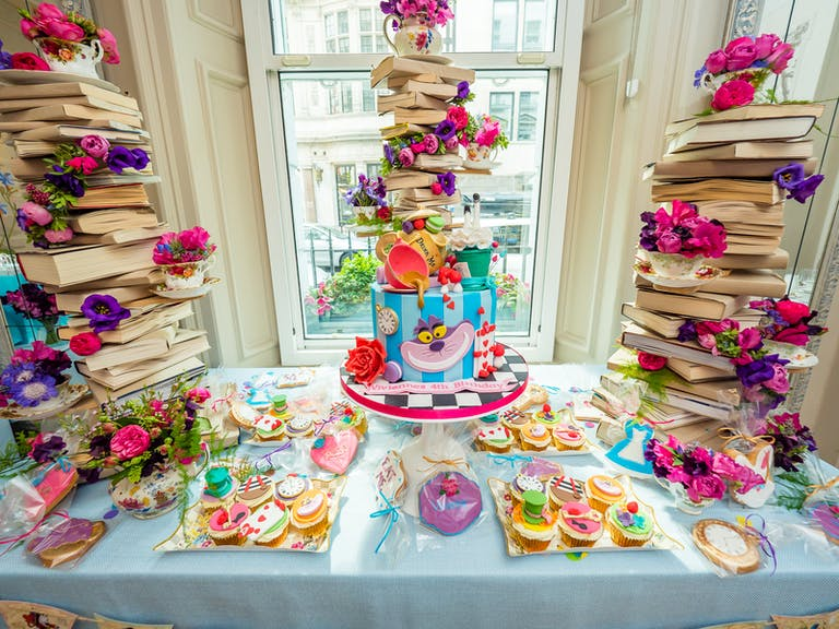 Kids 4th Birthday Alice in Wonderland Themed Tea Party Celebration with Mad Hatter and Chesire Cat Tiered Cake with Books On Top | PartySlate