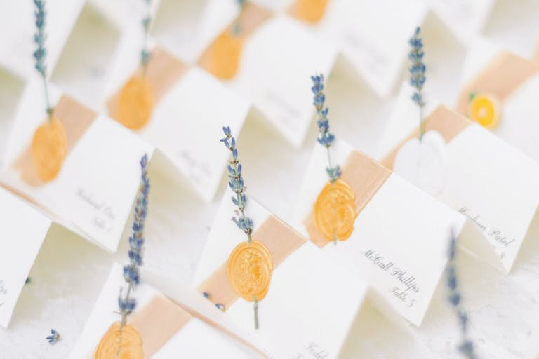 White Escort Cards With Gold Wax Seals and Sprigs of Lavender | PartySlate