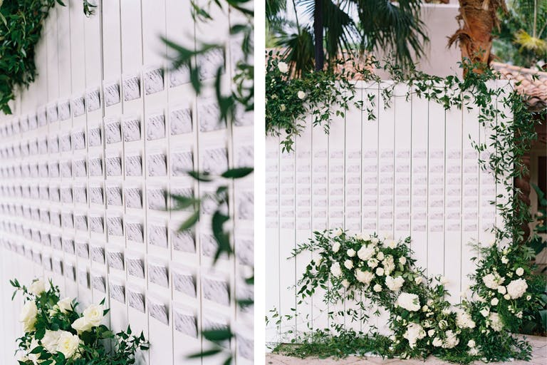 Marbled Escort Cards Attached To White Fence Backdrop With Greenery and White Flowers | PartySlate
