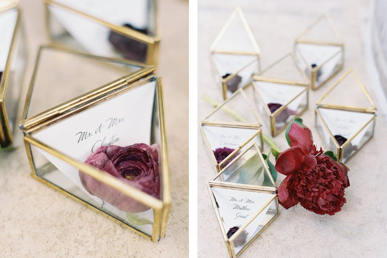 Diamond-Shaped Glass Jewelry Boxes Holding Red Flowers and Place Cards for Wedding Celebration | PartySlate