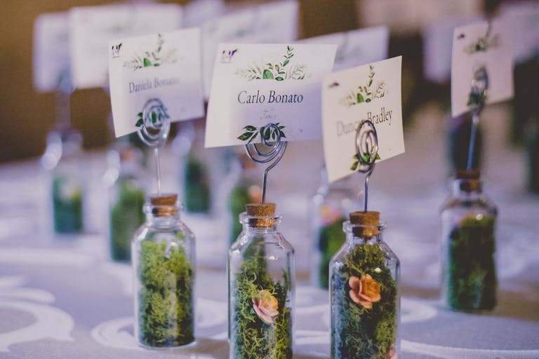 Wedding Escort Cards Attached to Miniature Bottles Filled With Moss and Tiny Flowers | PartySlate
