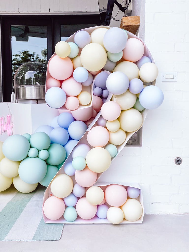 A Two Sweet Kids Birthday Party Celebration with Pastel Balloon Installation in the Shape of the Number Two | PartySlate