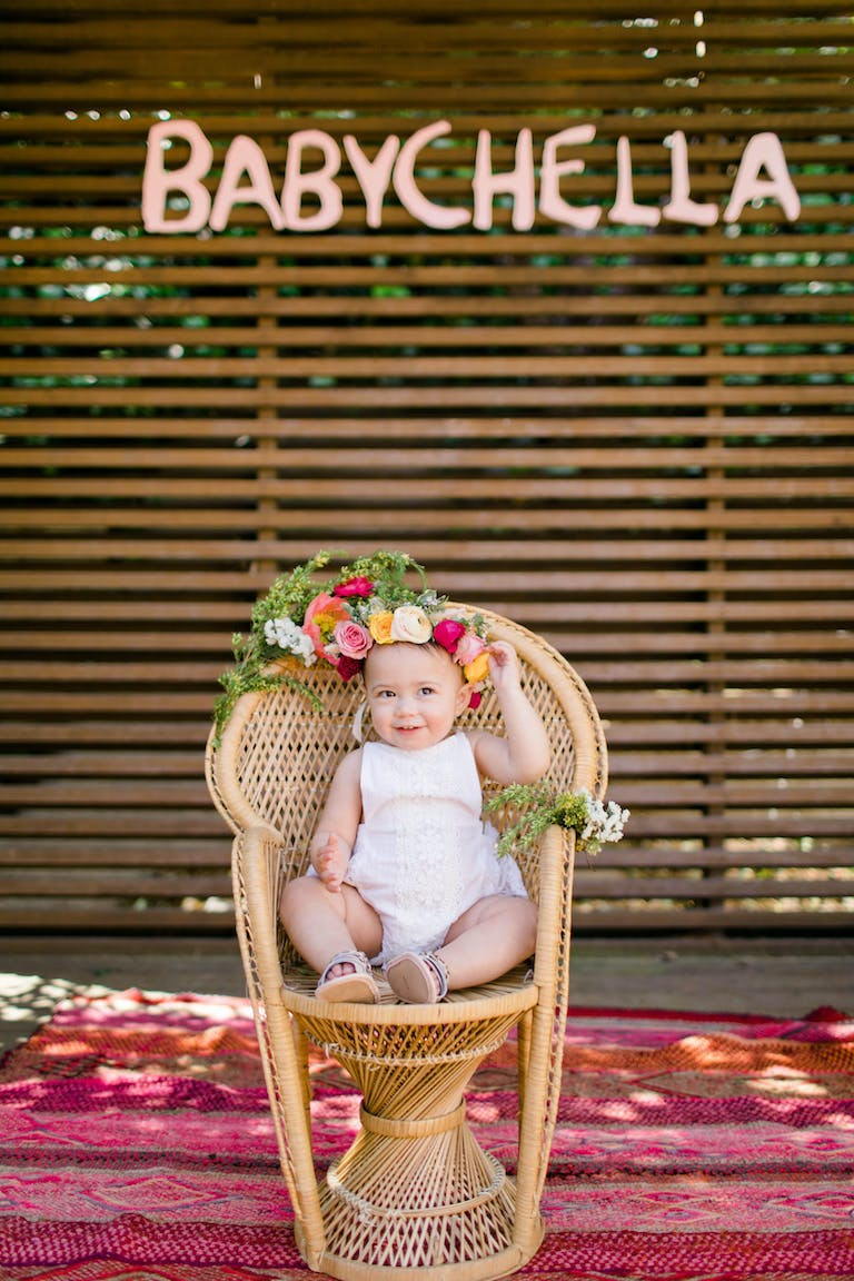 BabyChella Coachella Inspired Kids Birthday Party Idea with Baby Sitting in a Wicker Chair with a Flower Crown | PartySlate