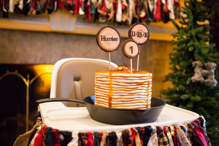 Kids Lumberjack Themed 1st Birthday Party with Flapjack Cake Sitting on a High Chair | PartySlate
