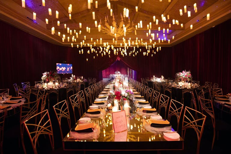 Glowing Candles are Suspended Over Mirrored Wedding Tablescape | PartySlate