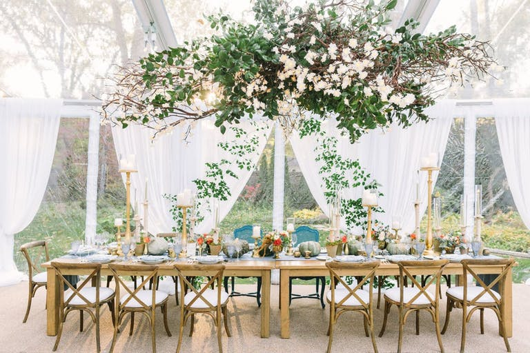 Rustic Wedding Tablescape With White Drapery and Overhanging Greenery   PartySlate