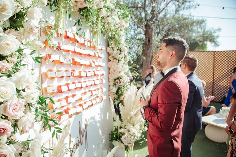 Man in Red Jacket Looks For His Wedding Seating Assignment at Floral-Framed Sign With Oranges and Place Cards | PartySlate
