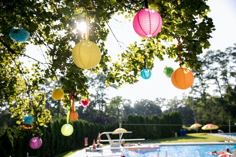 Colorful Paper Lantern in Tree Overhanging Private Party Pool | PartySlate