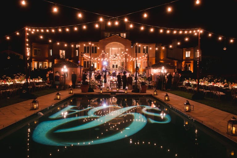Nighttime Party at Private Residence With String Lighting and Monogram Pool Décor | PartySlate