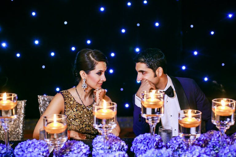 Bride and Groom Sit at Sweetheart Table Laden With Purple Hydrangea Wedding Centerpieces and Candlelight Against a Starlit Backdrop   PartySlate