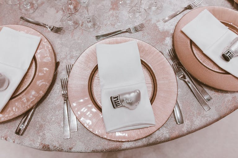 Shimmering Pink Wedding Tablescape With Personalized Mini Pink Boxing Glove Trinket on Each Plate | PartySlate