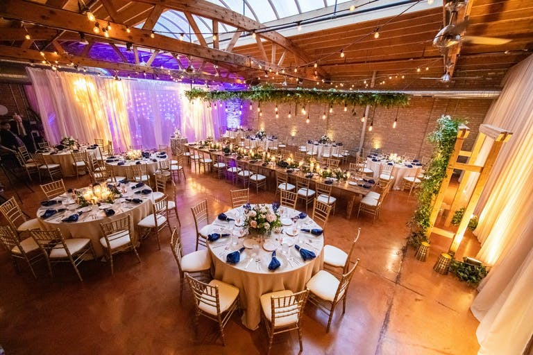 Wedding Reception at Loft on Lake in West Loop Chicago Featuring Green Foliage and Creative Wall Lighting | PartySlate