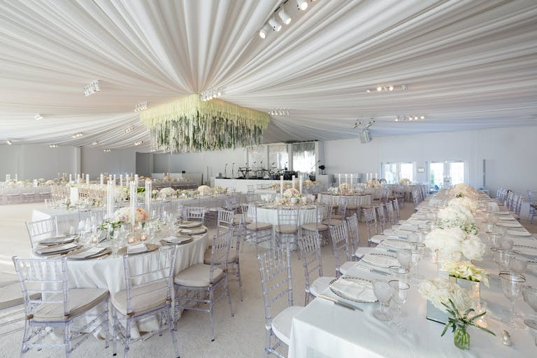 All-White Wedding Tent With Sheer Ceiling Drapery and Suspended Square Floral Focal Point | PartySlate