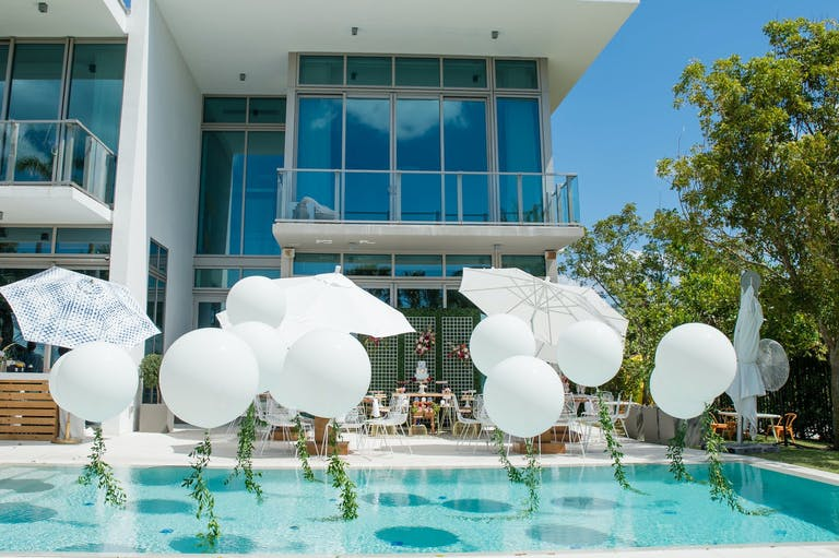 Pool With White Balloon and Garlanded String Installation | PartySlate
