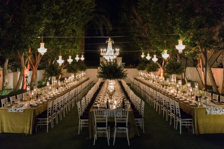 Nighttime, Outdoor Wedding Reception With Three Long Tables in Yellow Linen and Suspended Chandeliers with Greenery | PartySlate