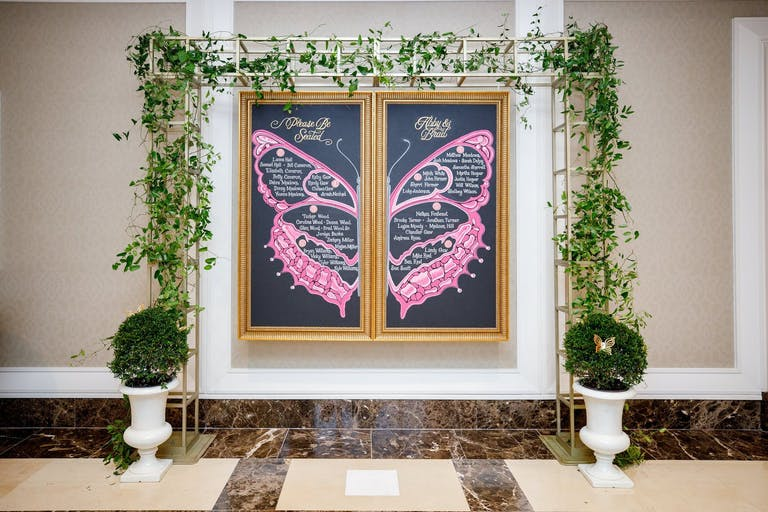 Chalk Signage With Butterfly Design and Wedding Seating Assignments | PartySlate