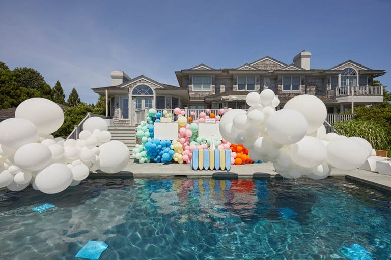 Poolside Dr. Seuss-Themed Baby Shower at Private Residence with White Cloud Balloon Installation Hovering Over Pool and Colorful Balloon Backdrop | PartySlate