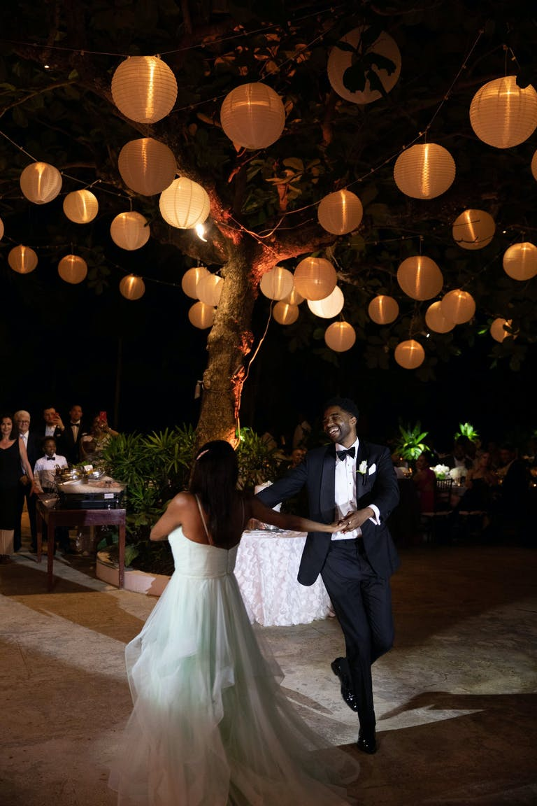 Bride and Groom Dance in Front of a Tree Laden With Globed Paper Lanterns | PartySlate