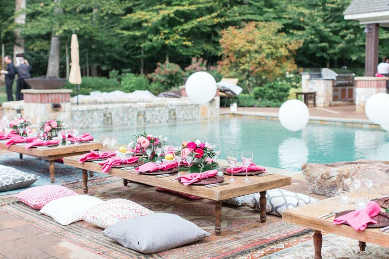 Poolside Low Tablescapes With Pink Flowers and Pillow Seating | PartySlate