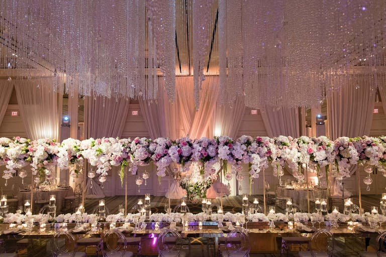 Ballroom Wedding Reception With Elevated White and Purple Floral Centerpieces and Suspended Crystal Wedding Ceiling Decorations | PartySlate