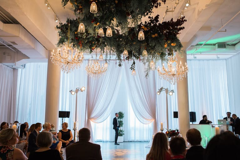 White Wedding Ceremony With Pillars, Sheer Draper, and Ceiling Installation of Greenery and Lighting | PartySlate