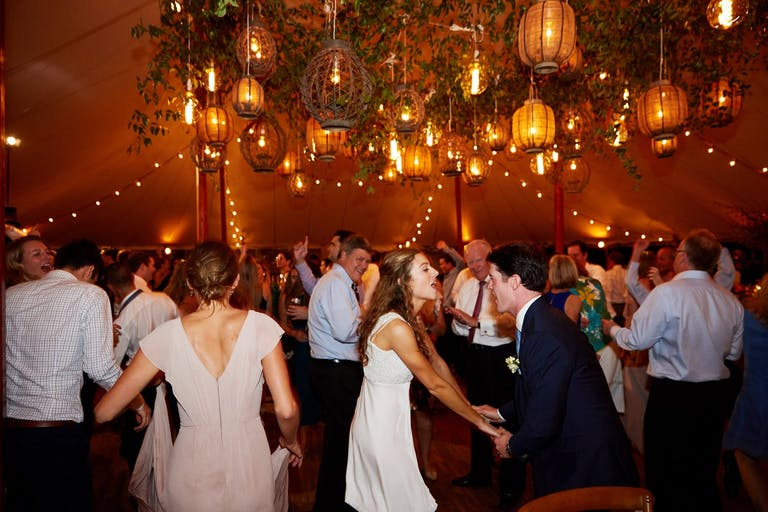 Bride, Groom, and Guests Dance in Tented Venue With Basket-Woven Lanterns and Greenery Ceiling Décor | PartySlate