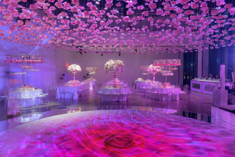 Pink-Toned Wedding With Bright Rose-Patterned Dance Floor and Suspended Pink Bloom Ceiling Installation | PartySlate