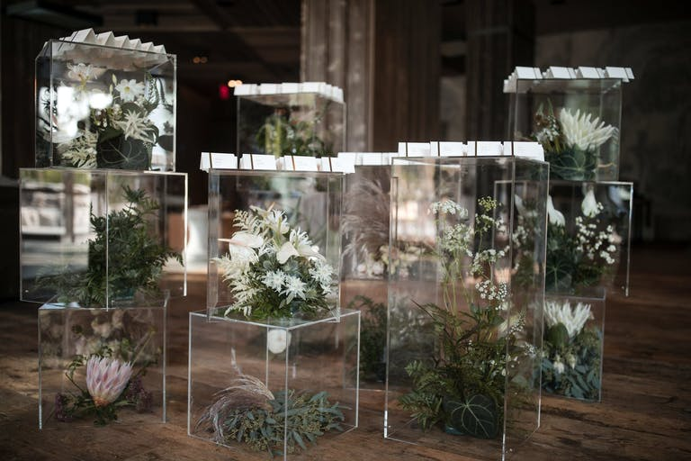 Lucite Boxes Filled With Tropical Flowers and Topped with White Wedding Escort Cards | PartySlate