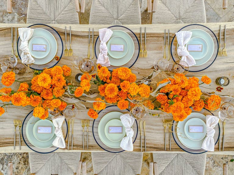 Wooden Table With Orange Wild Flowers and Pale Green Dishware | PartySlate